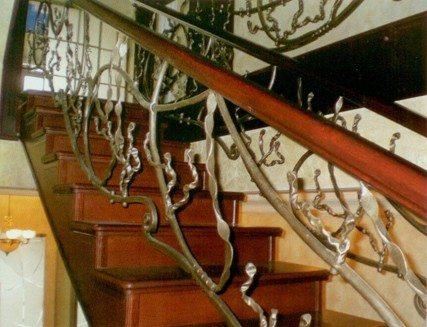Деревянные поручни на кованой лестнице