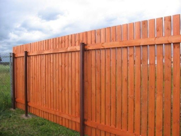 Деревянный забор на металлических опорах.