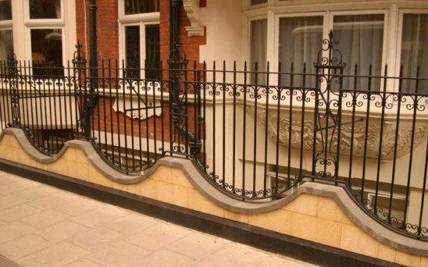 Фото – Комбинированное ограждение из бетона и кованых элементов.