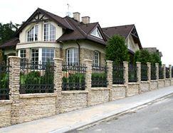 Фото комбинированного забора с каменными колоннами, коваными секциями и живой изгородью