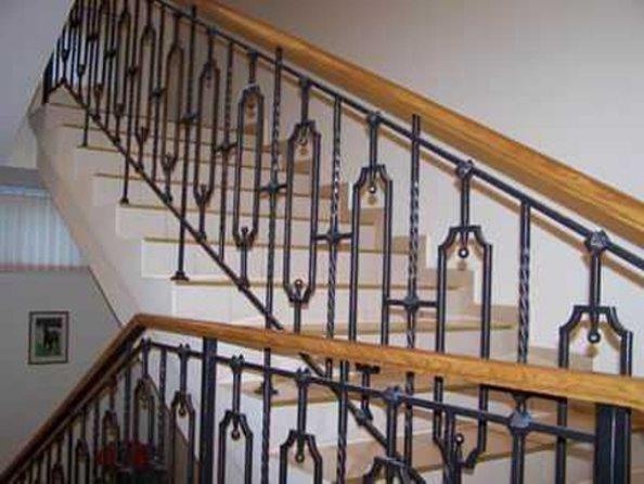 Художественная ковка ограждения для лестниц отлично сочетается с деревянными перилами.