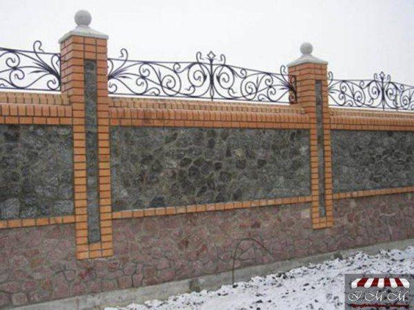 Кирпичный забор, облицованный диким камнем с установленными коваными элементами