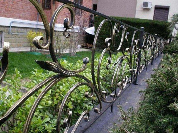 Кованая ограда не только защищает, но и украшает газон.