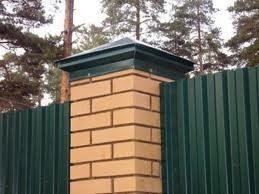 Металлическая шапка на забор с кирпичными столбами.