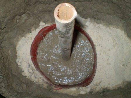На данном фото показаны параметры установки металлического опорного столба и наглядный процесс заливки бетоном