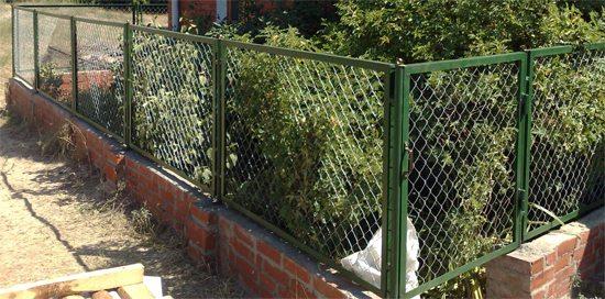 На этом фото секционный забор из рабицы установлен на кирпичное основание, что позволяет увеличить высоту изгороди, сделав её прочнее и привлекательнее.