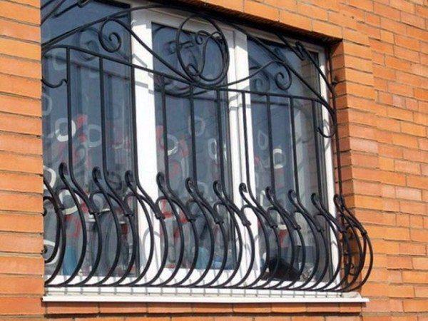 На фото пример кованой решетки на окна