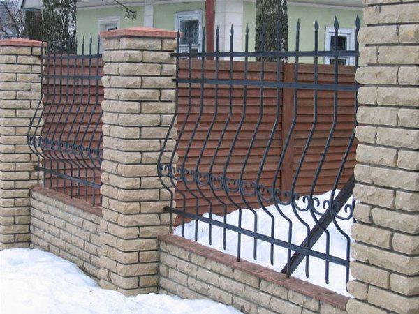 Незыблемый и изысканный кованый забор с кирпичными столбами.