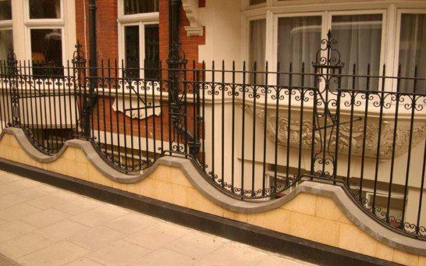Оригинальная ажурная ограда из металла с элементами ковки и волнообразным основанием