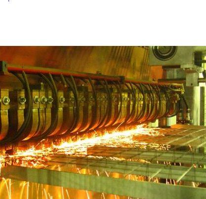 Процесс контактной сварки стальных прутьев при производстве сварной сетки.