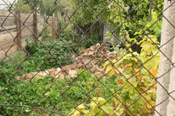 Со стороны проезда - сплошной забор из досок. Между участками стоит сетчатое ограждение, не затеняющее растения