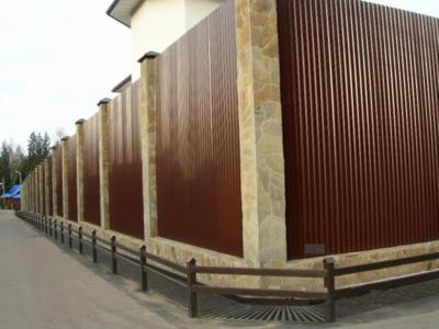 Умелое сочетание цвета и размера листов профнастила с основанием, столбиками и элементами декора позволяют создать идеальный по своим внешним качествам забор для частного дома