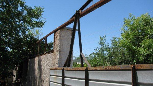 Ворота не опираются на тележки, а висят на уложенном поверх ограждения швеллере, усиленном в середине сварной фермой.