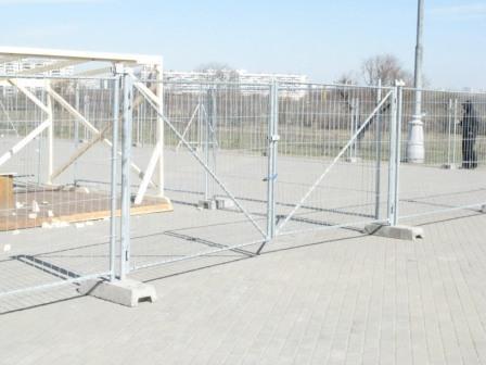 Временная оградительная секционная конструкция, состоящая из квадратов, прутков и бетонных блоков