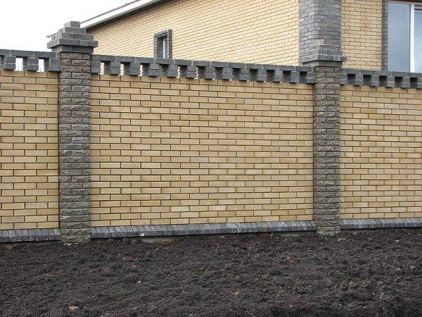 Забор из облицовочного кирпича, украшенный вставками из плитки, имитирующей дикий камень