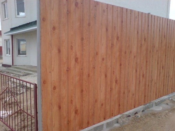 Забор под дерево из профнастила практически не отличим от натурального материала.