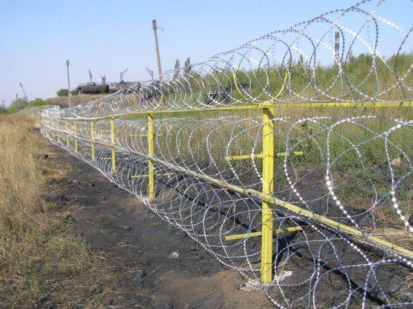 Забор с колючей проволокой даже не требует особых капитальных вспомогательных приспособлений, по крайней мере, дизайнерская сторона вопроса отходит на второй план