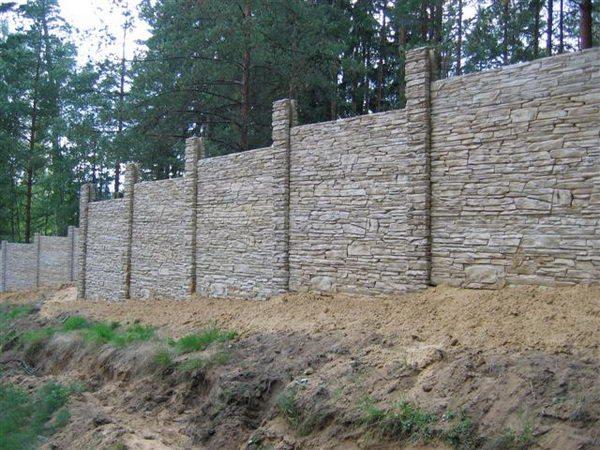 Задача, как построить каменный забор усложняется, если траектория установки «прыгает» по высоте. Тогда не обойтись без значительных грунтовых работ, точного расчёта и предварительной установки столбов.