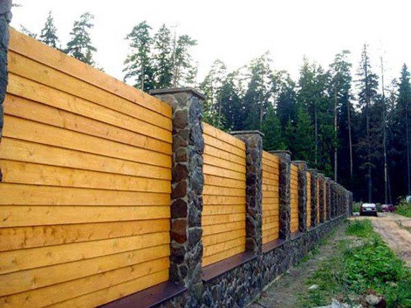 Деревянный забор с каменным основанием и столбами.