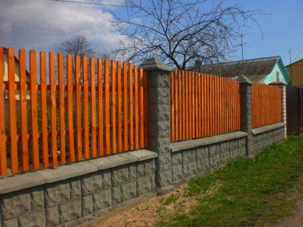 Дизайнеры успешно используют вверху деревянные секции в виде частокола или просто внахлест размещенные между бетонными столбами.