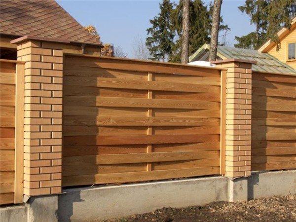 Дощатый плетёный забор с кирпичными столбиками