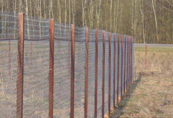 Ограда из сетки на деревянных столбах