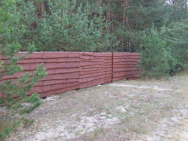 После покраски ограда из горбыля выглядит следующим образом.