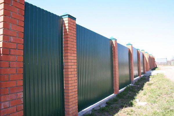 Забор из профилированных листов и кирпичных столбиков со стальными крышками