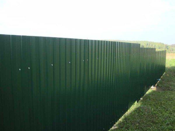 Здесь строители экономили свое время и вкрутили саморезы через две волны. В сильный ветер забор будет дребезжать.